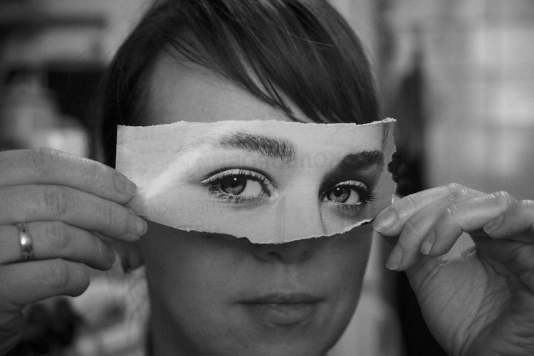 Close-up of woman holding torn paper eyes over face