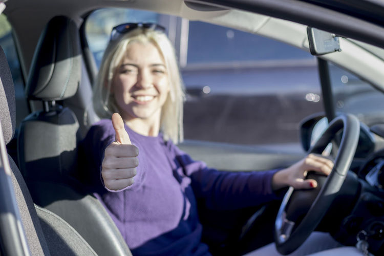 Portrait of smiling woman gesturing thumbs up sign while sitting in car