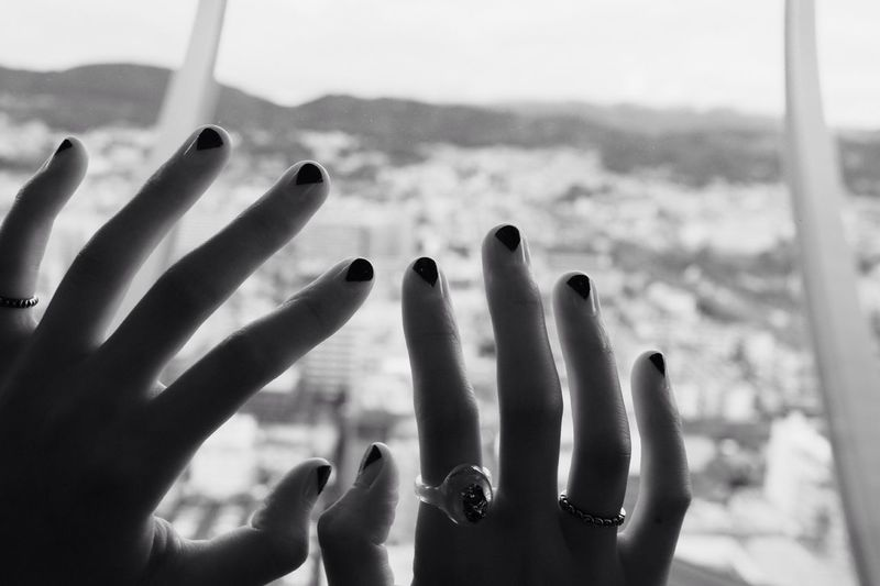Close-up of hands on glass window