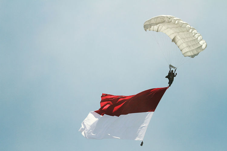Low angle view of man with flag paragliding against clear sky