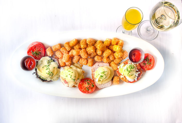 Eggs Benedict for Brunch Eggs Benedict Breakfast Breakfast Close-up Day Drink Egg Eggs Benedict Eggs Benedit Food Food And Drink Freshness Fried Egg Hashbrowns Healthy Eating Indoors  No People Plate Ready-to-eat Serving Size Table Tatertots Tomato White Background