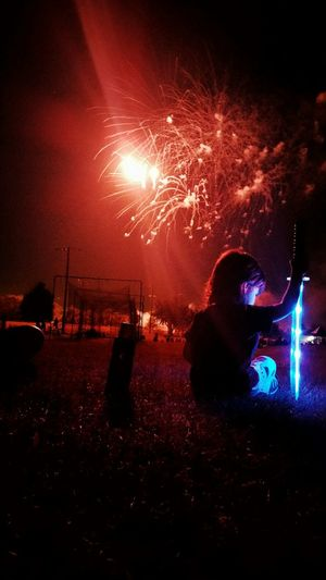 Boy Holding Illuminated Laser Sword While Sitting On Field Against Firework Display At Night