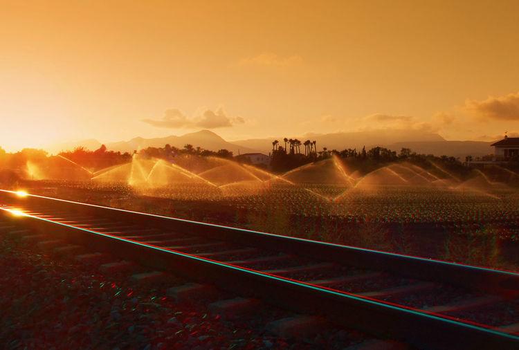 Railroad track by farm against orange sky