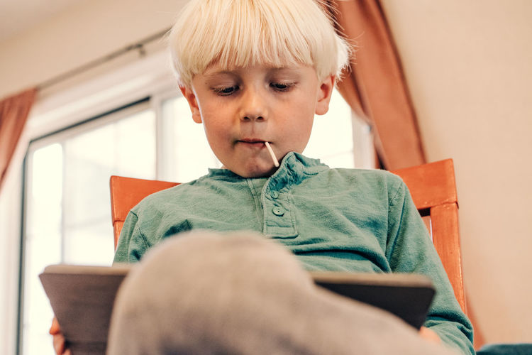 Boy sitting on chair at home