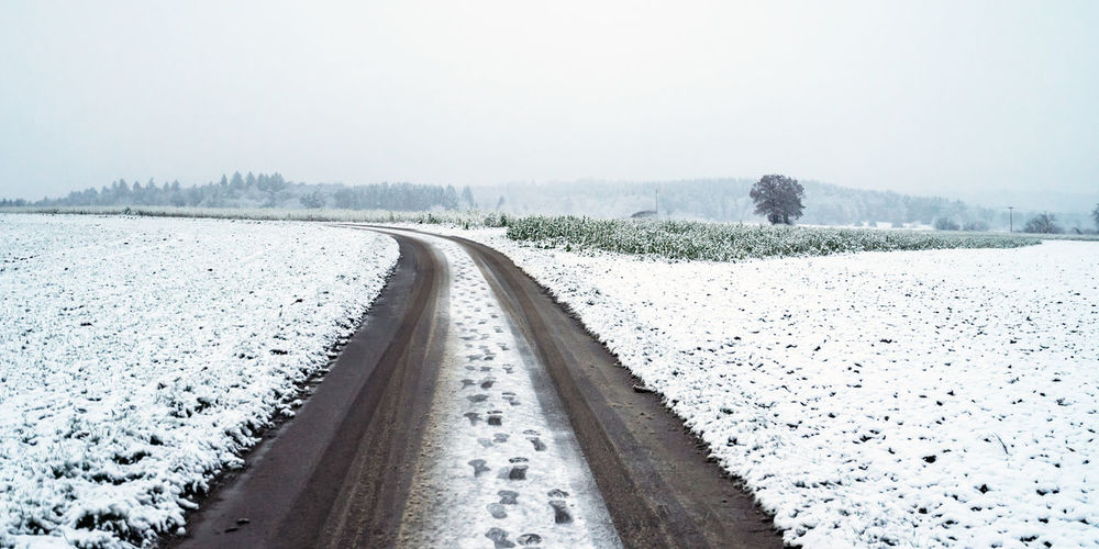 Tire tracks on snow covered field against sky