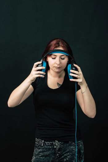 Young Woman Listening To Music Against Black Background