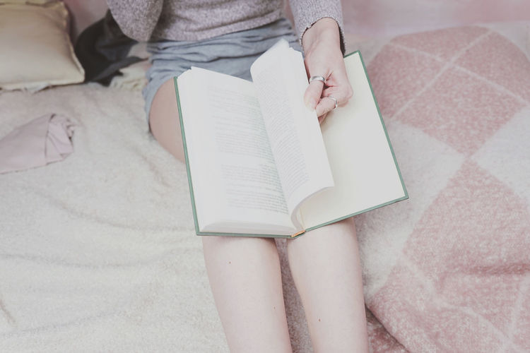 Human Body Part One Person Real People Publication Book Midsection High Angle View Bed Body Part Furniture Women Indoors  Human Hand Reading Low Section Lifestyles Holding Hand Human Leg Studying KAWAII Smart Phone Intelligence Literature