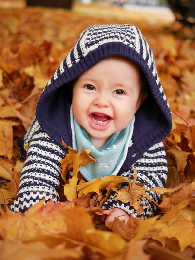 Cute baby girl lying on autumn leaves