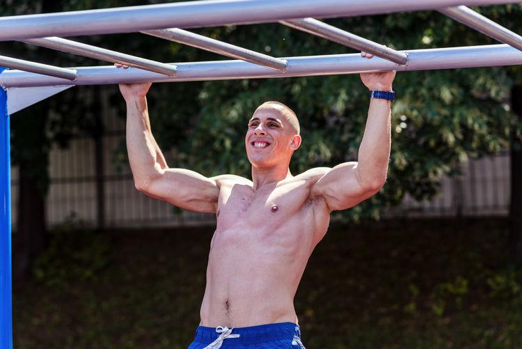 Shirtless muscular man exercising while hanging on monkey bars