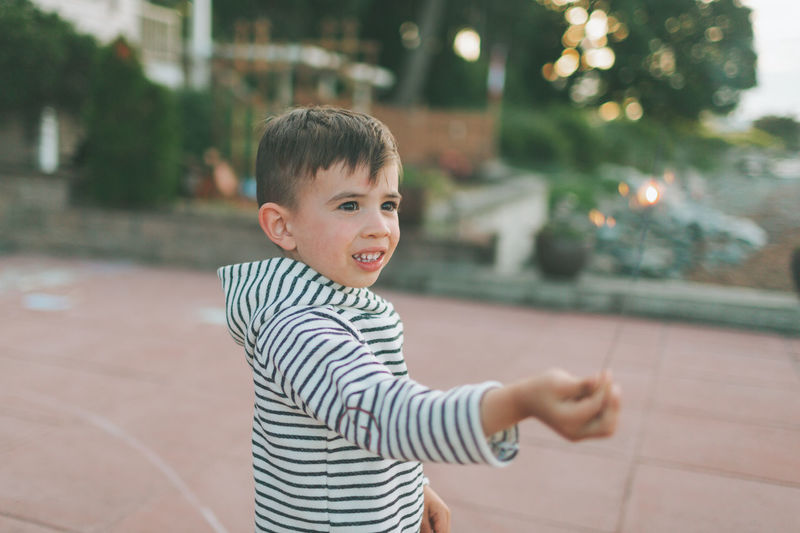 Cute boy holding sparkler while standing outdoors