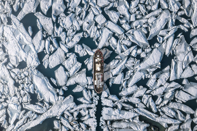 Aerial view of ship amidst glacier in sea