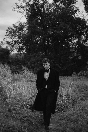 a Young Man walking in a field Man Portrait Of A Woman Adult Blackandwhite Field Front View Full Length Grass Land Lifestyles Looking At Camera Nature One Person Outdoors Plant Portrait Real People Standing Teenager Tree Walking Women Young Adult Young Women