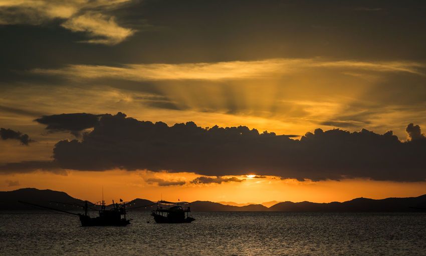 Silhouette Boats In Sea Against Dramatic Sky During Sunset