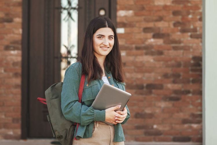 Portrait of young female student with beautiful smile using tablet in college or private school