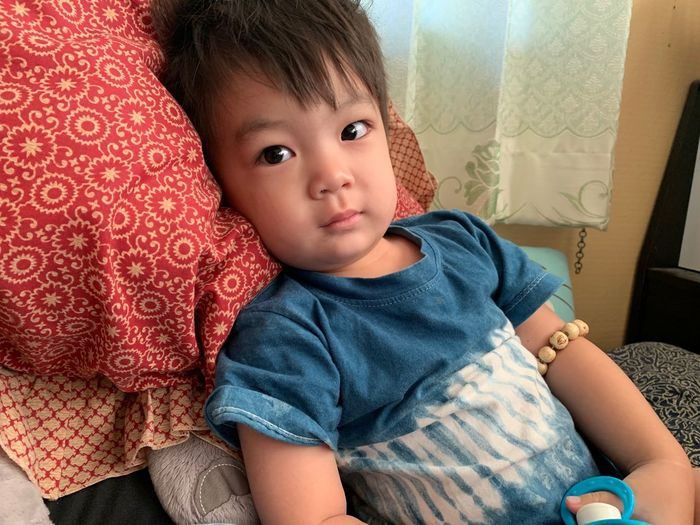 Child Childhood Real People Sitting Indoors  Cute Innocence Front View One Person Casual Clothing Furniture Lifestyles Males  Boys Portrait Men Home Interior Three Quarter Length