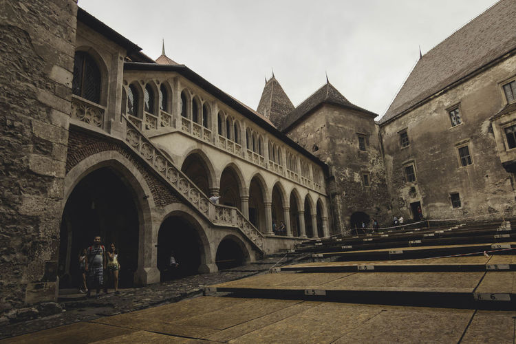 Arcade Arch Architectural Column Architecture Building Exterior Built Structure Castle City Life Day Entrance Façade Famous Place Footpath History Hunedoara Incidental People Old Town Outdoors Sky Steps The Past Tourism Transylvania Travel Destinations