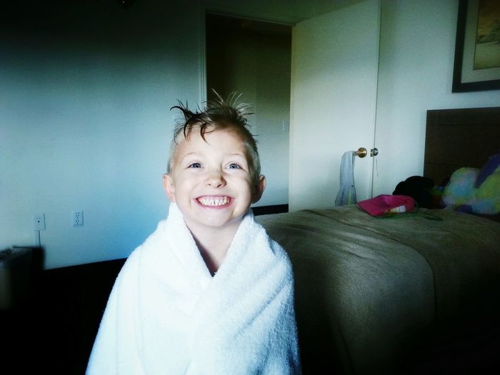 Smiling Boy Wrapped In Towel At Home