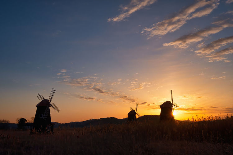Silhouette traditional windmill on field against sky during sunset