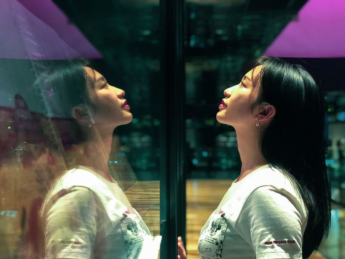 Close-up of young woman looking away while standing by glass window at night