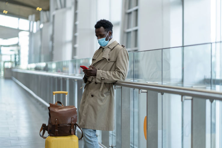 Man wearing mask using smart phone at airport