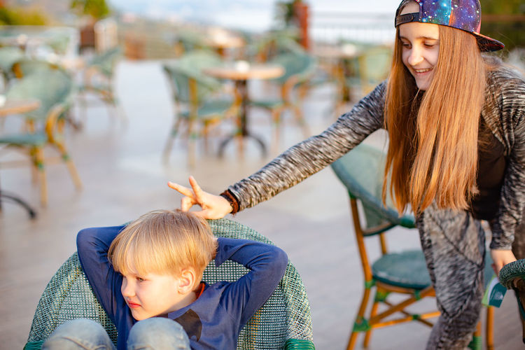 Teenage girl doing rabbit ears gesture on brother head