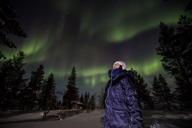 Man on snow covered landscape against sky at night