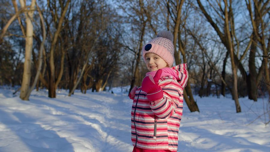 Girl wearing mask on field during winter