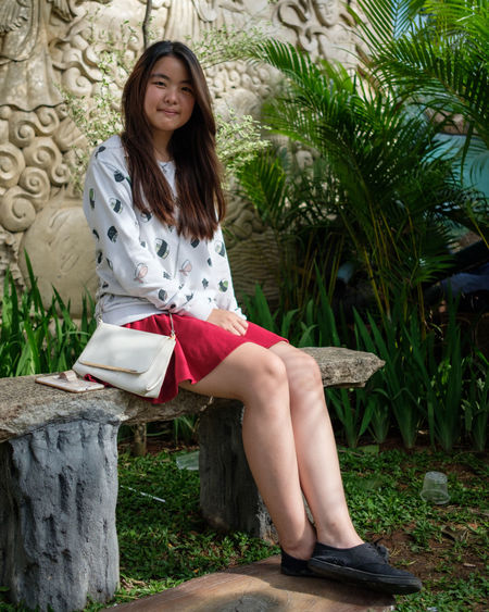 Portrait of smiling young woman sitting on bench in park