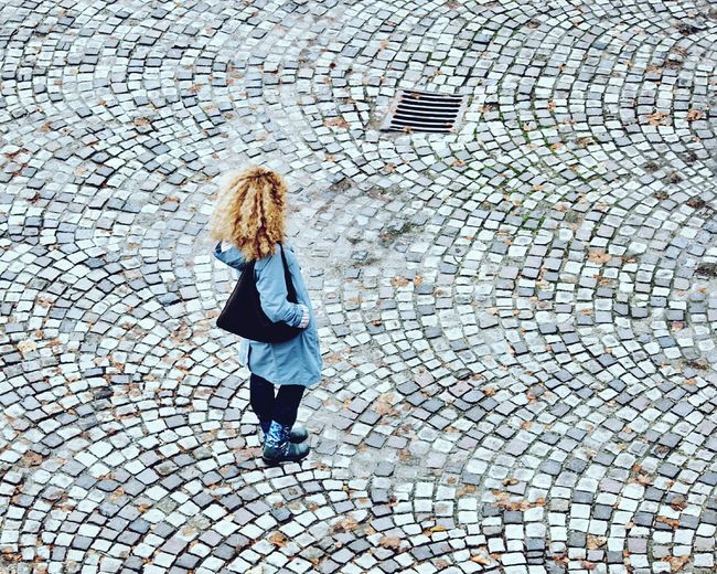 High Angle View Of Woman Standing On Cobblestone Street