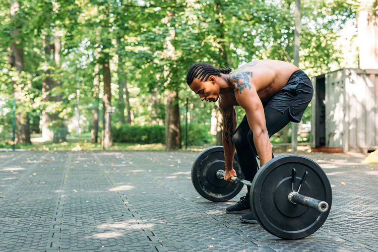 Shirtless young man holding barbell outdoors