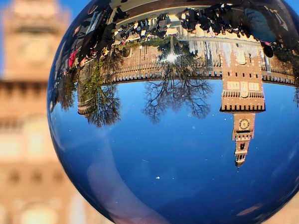 Sun Clear Sky Art Beauty Castle Trees Upside Down Reflection Ball Glass EyeEm Selects Close-up Text Communication Reflection No People Western Script Sphere Focus On Foreground Blue Glass - Material Outdoors Day Geometric Shape Single Object Nature Water Circle Shape