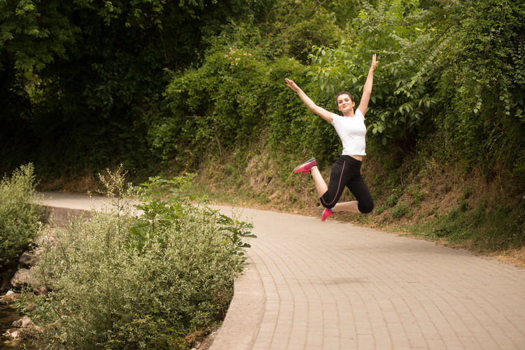 Young woman jumping on tree
