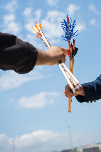Low Angle View Of Hands Holding Arrows Against Blue Sky