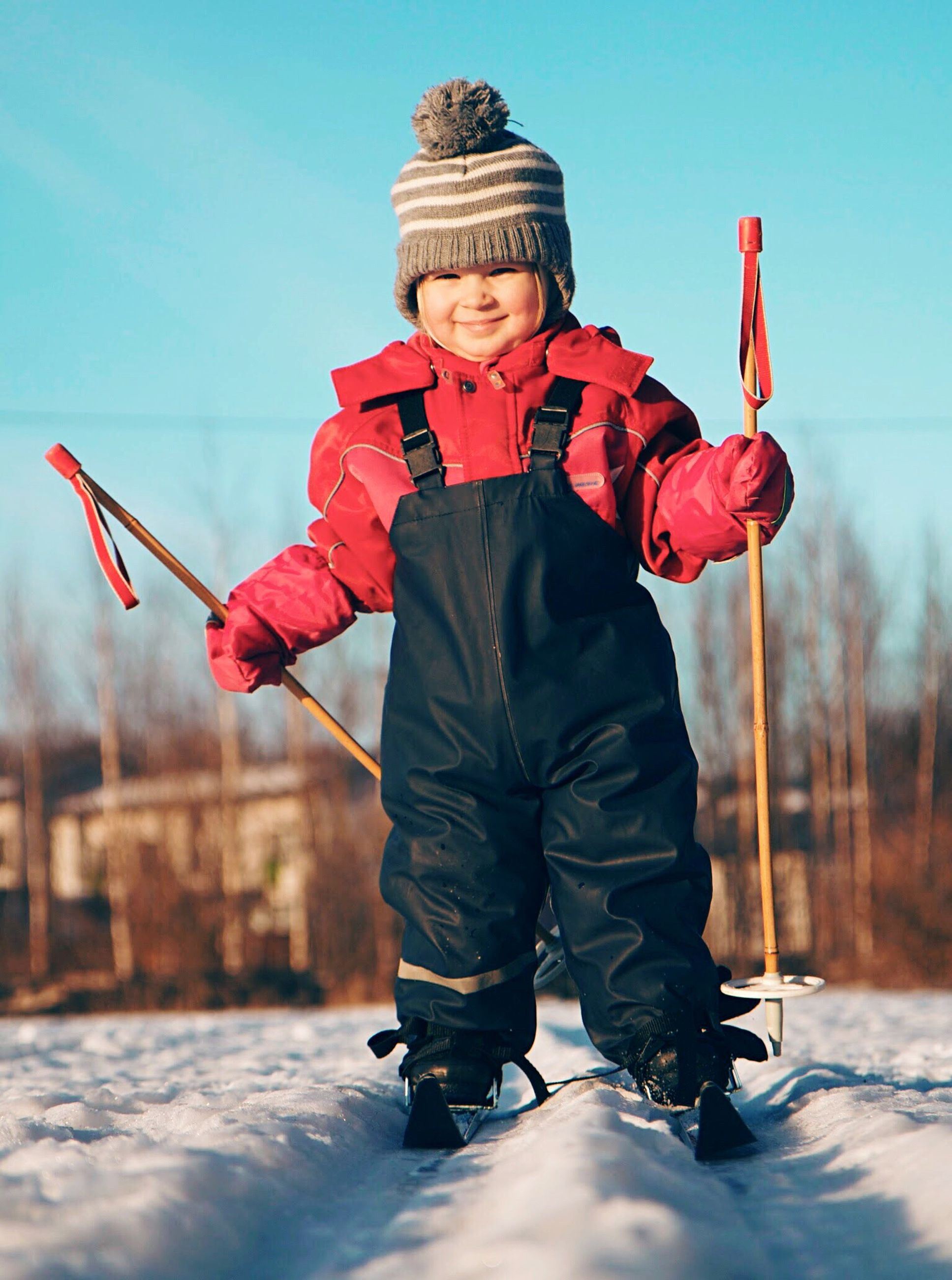 winter, warm clothing, one person, snow, males, children only, child, red, full length, cold temperature, one boy only, childhood, front view, standing, looking at camera, people, outdoors, knit hat, portrait, smiling, ski holiday, cheerful, sky, nature, human body part, snowboarding, day
