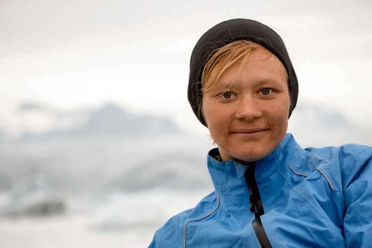A woman in a hat and a jacket look at the camera with icebergs and mountains in the background. Adult Adults Only Day Hat Headshot Human Body Part Human Face Jacket Looking At Camera One Person Outdoors People Portrait Winter Woman Young Adult