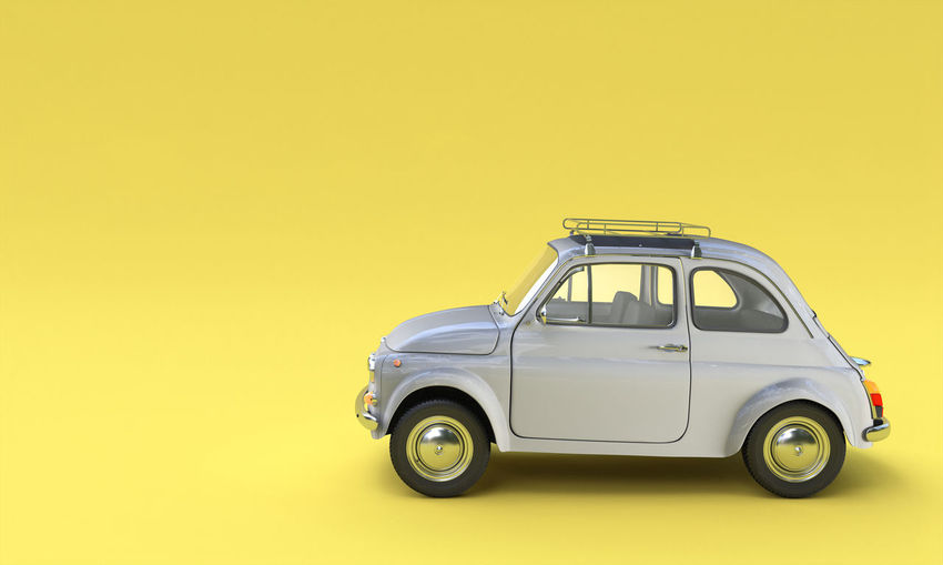 Side view of toy car against yellow background