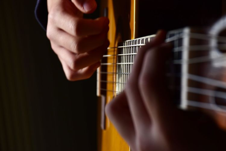 Youngster playing classic guitar. closeup of hands