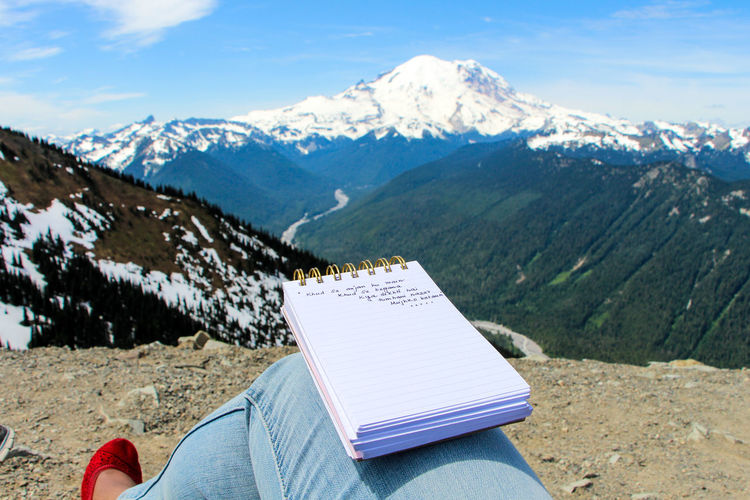 Person writing journal against mountains