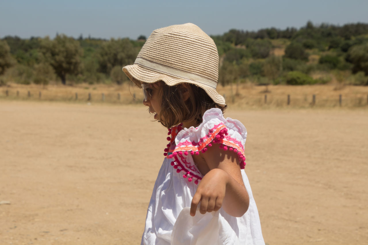 real people, field, one person, childhood, sand, leisure activity, outdoors, focus on foreground, lifestyles, girls, day, standing, sunlight, elementary age, nature, sun hat, beach, landscape, tree, sky