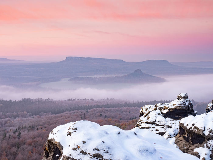 Snowy rocks above valley in saxony switzerland national park. elbe river valley in chill morning