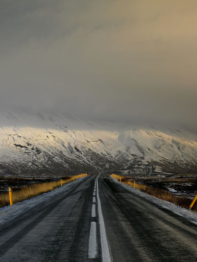 Road leading towards mountain against sky during winter