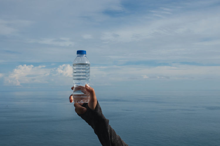Person holding bottle in sea against sky