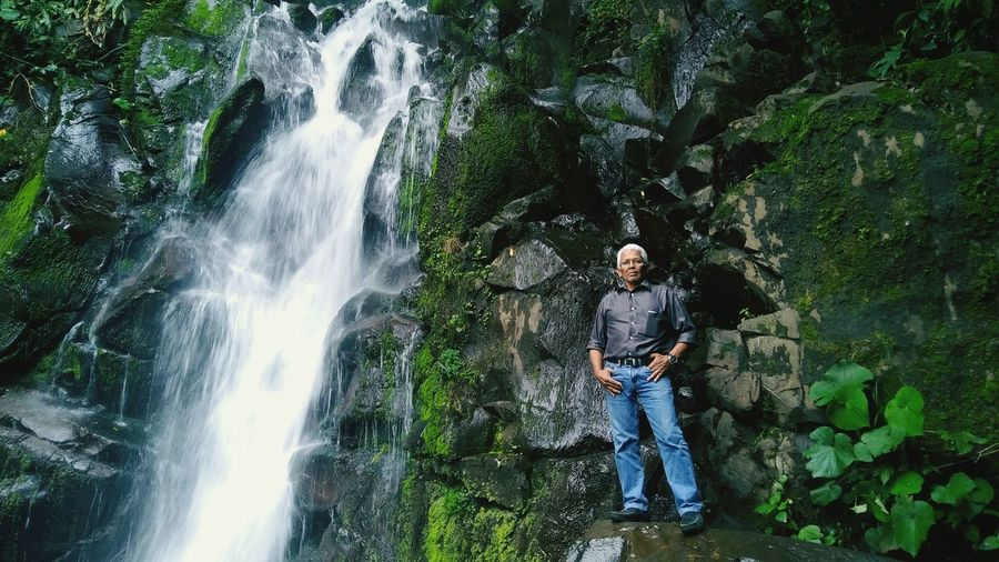 Low angle view of mature man standing on rock by waterfall