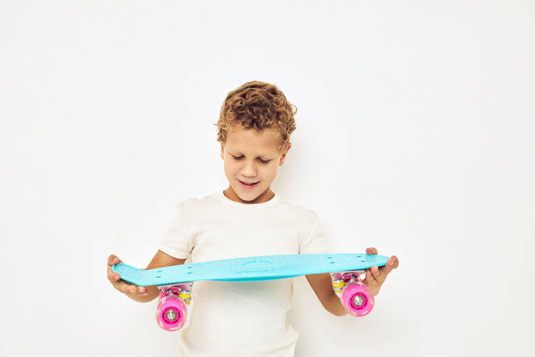Boy playing with toy against white background