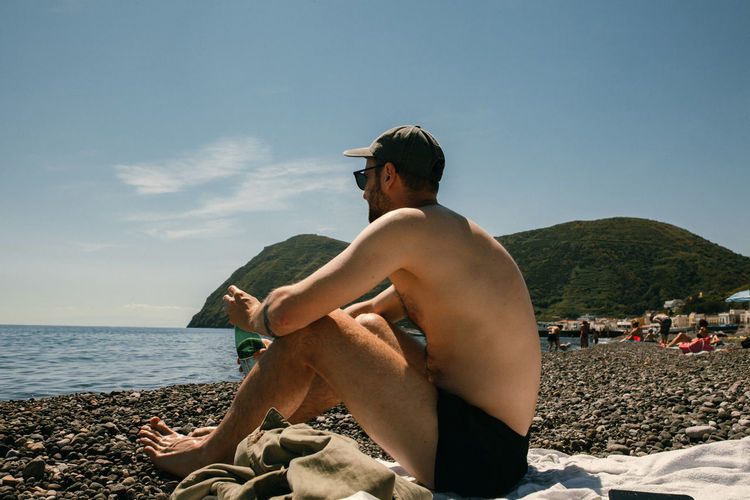 Full length of shirtless man sitting on beach against sky