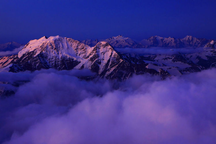 Scenic View Of Snowcapped Mountains Covered With Cloudscape At Dusk