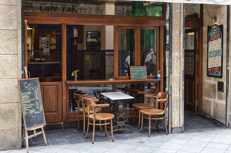 Empty chairs and tables at sidewalk cafe outside building