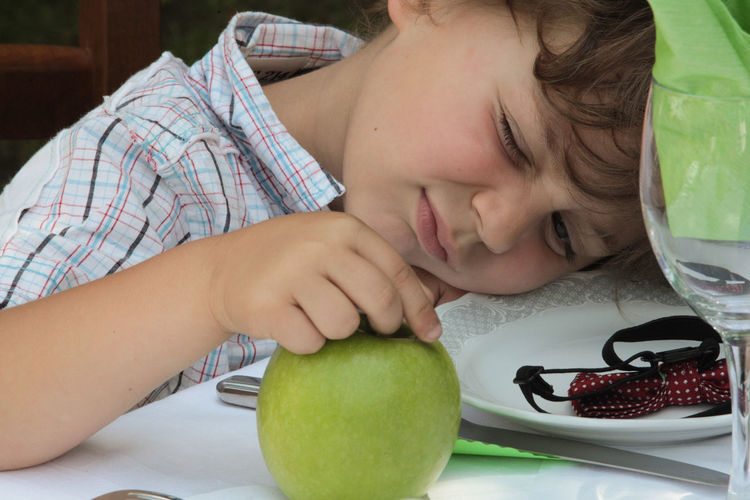 Portrait of cute boy with apple