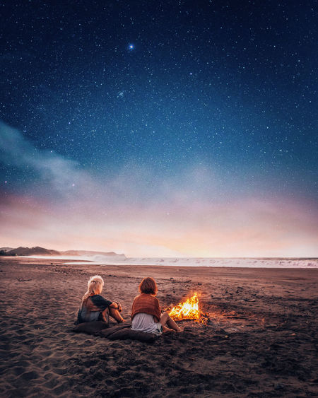 Women Sitting By Bonfire At Beach Against Sky