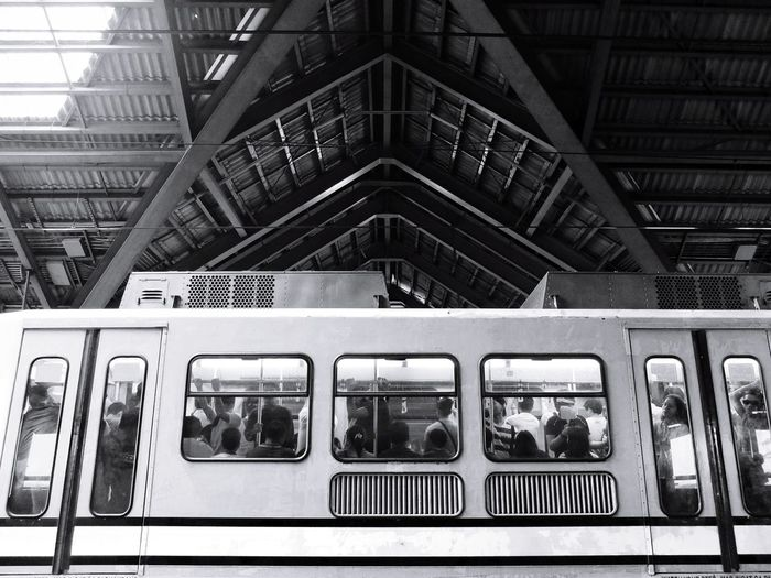 Low angle view of people traveling in train at station